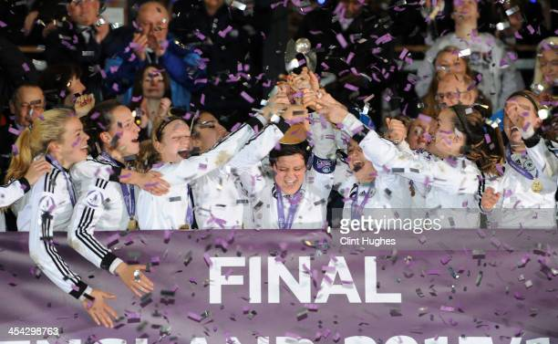 Germany captain Jasmin Sehan holds up the trophy as her teammates celebrate their victory during the UEFA European Women's Under 17 Championship...