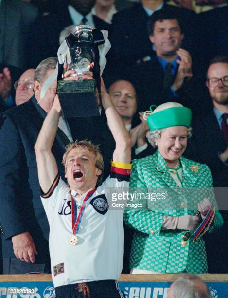 Germany captain Jurgen Klinsmann lifts the trophy as Her Majesty Queen Elizabeth II smiles after the 1996 UEFA European Championships Final against...