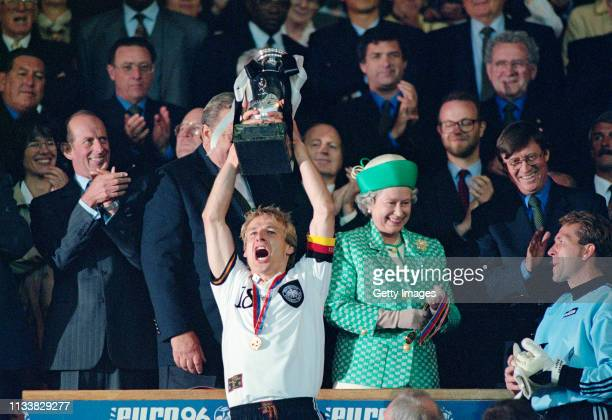 Germany captain Jurgen Klinsmann lifts the trophy as Her Majesty Queen Elizabeth II smiles and goalkeeper Andreas Kopke looks on after the 1996 UEFA...