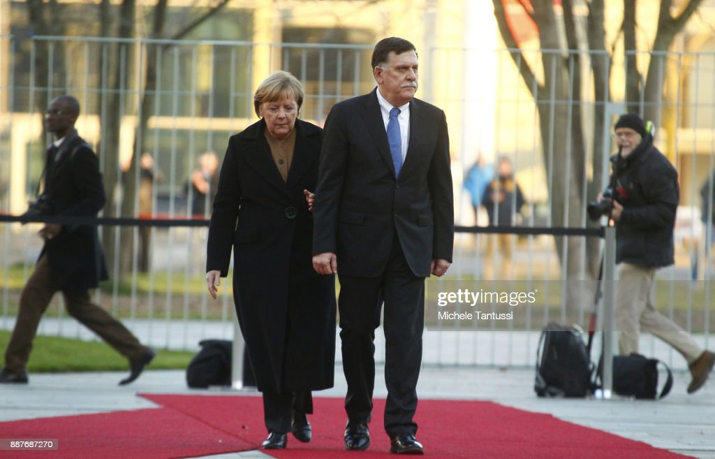 Germany Chancellor Angela Merkel and Chairman of the Presidential Council of Libya and prime minister Fayez Mustafa al-Sarraj pass by the honor guard in the Courtyard of the German Chancellery ahead of their meeting on December 7, 2017 in Berlin, Germany. The Libyan leader meets Merkel to discuss the political situation of both states relationship, focusing on finding a better way to solve the refugees issue.