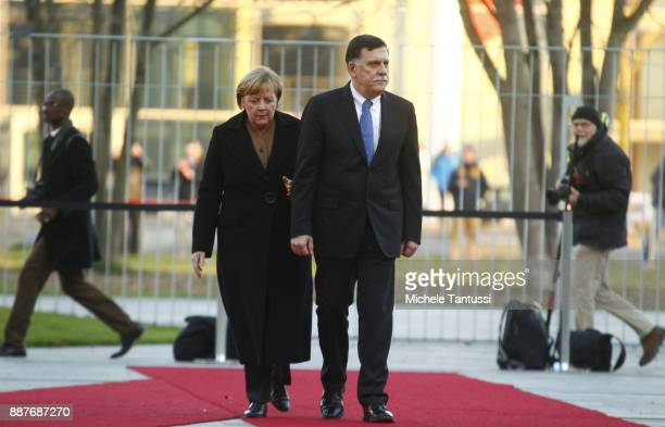 Germany Chancellor Angela Merkel and Chairman of the Presidential Council of Libya and prime minister Fayez Mustafa al-Sarraj pass by the honor guard...