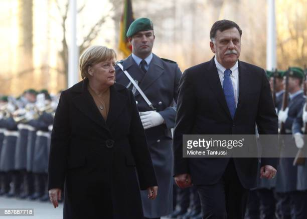 Germany Chancellor Angela Merkel and Chairman of the Presidential Council of Libya and Prime Minister Fayez Mustafa alSarraj pass by the honor guard...