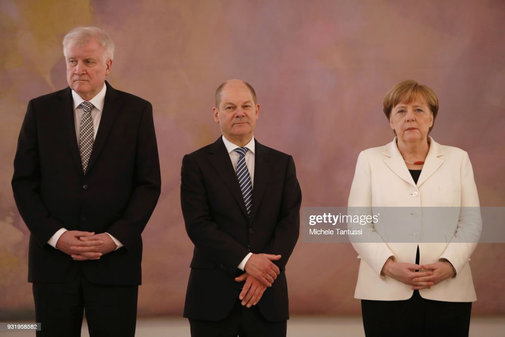 Germany Chancellor Angela Merkel stands near finance Ministry and vice Chancellor, Olaf Scholz and Interior Ministry, Horst Seehofer as she takes her oath to serve as Chancellor following the election by the Bundestag on March 14, 2018 in Berlin, Germany. Members of the new German government, a coalition between Christian Democrats (CDU/CSU) and Social Democrats (SPD), were sworn in today and will begin work immediately. The new government took the longest to create of any government in modern German history following elections last September that left the German Christian Democrats (CDU) as the strongest party but with too few votes in order to have a strong hand in determining the next coalition.