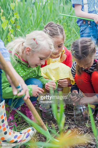 Germany, Children collecting worms in nature