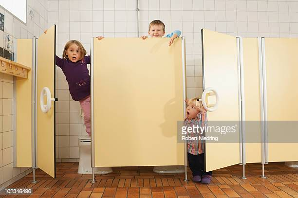 Germany, Children fooling about in public toilet