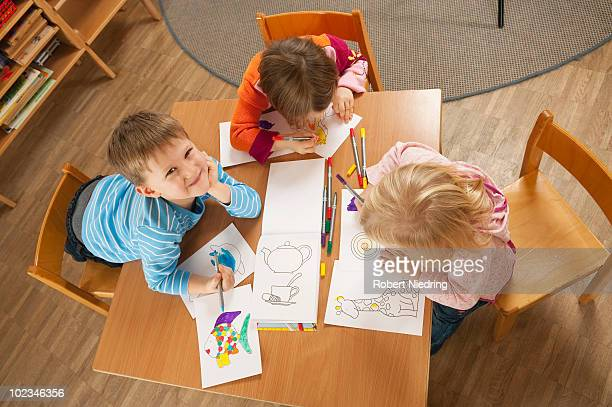 Germany, Children (2-5) sitting at table drawing pictures, elevated view