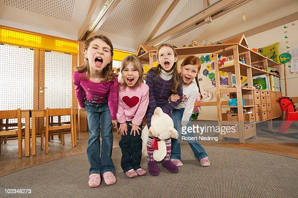 germany, children in nursery standing side by side screaming, portrait - only girls stock pictures, royalty-free photos & images