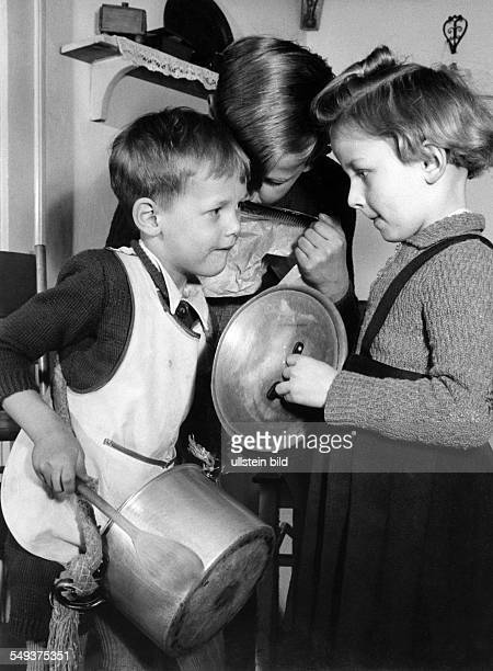 Germany Children playing with the verseels and pots of the kitchen 'House concert' in the fifties