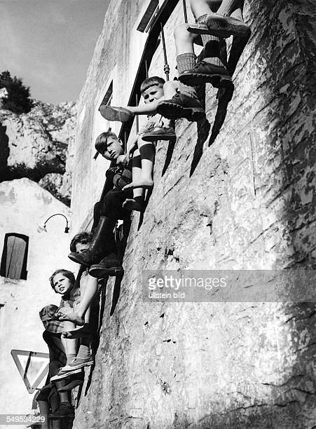 Germany children sittling on a wall with dangling legs about 1955