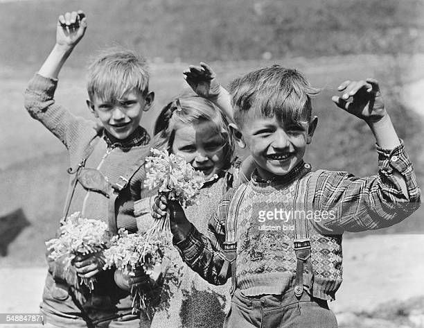 Germany children waving with a bunch of flowers