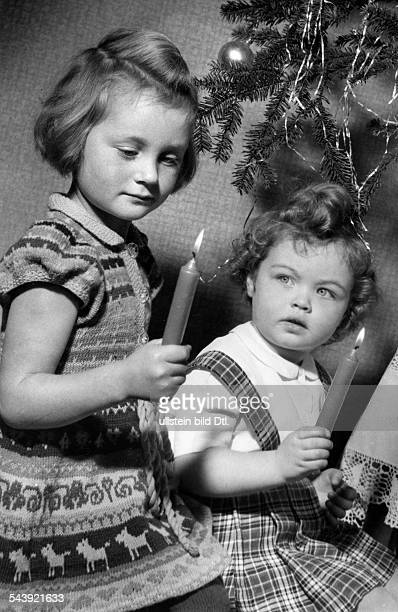 Germany Children with candles on the christmas tree Photographer Charlotte Willott 1953Vintage property of ullstein bild