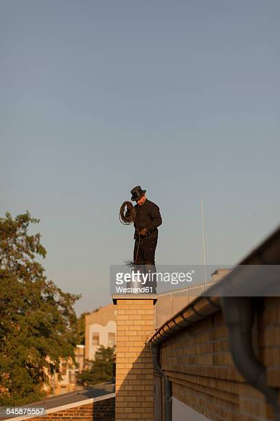 Germany, chimney sweep at work on rooftop