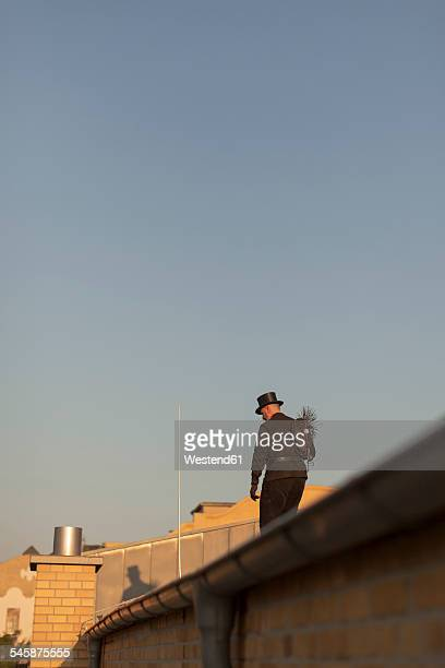 Germany, chimney sweep on rooftop