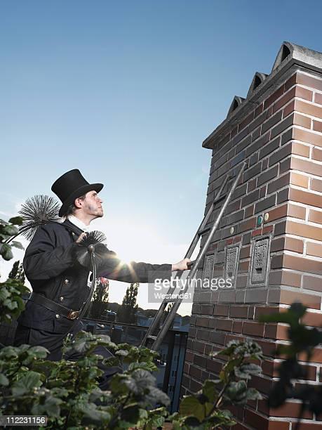 germany, chimney sweep with broom climbing ladder - schornsteinfeger stock-fotos und bilder