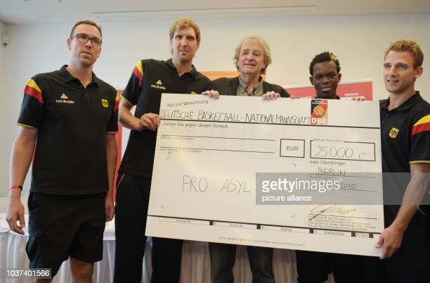 Germany coach Chris Fleming and players Dirk Nowitzki Dennis Schroeder and Heiko Schaffartzik hand over a cheque for 25000 euros to deputy manager of...