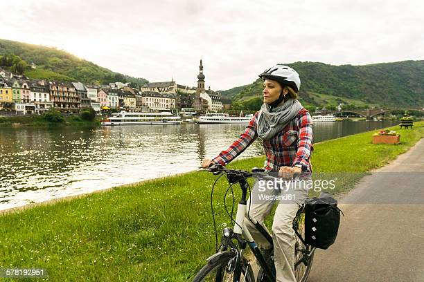 germany, cochem, woman riding bycicle along riverside of moselle - moseltal stock-fotos und bilder