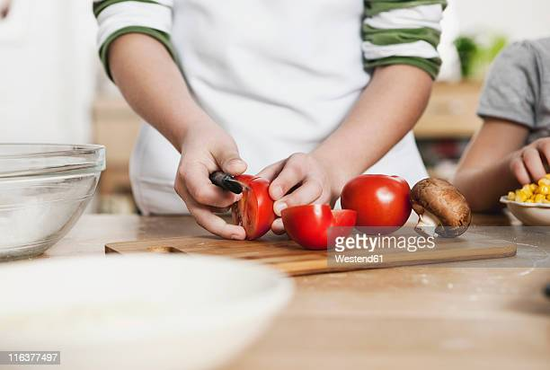 germany, cologne, boy cutting vegetables - children only stock pictures, royalty-free photos & images