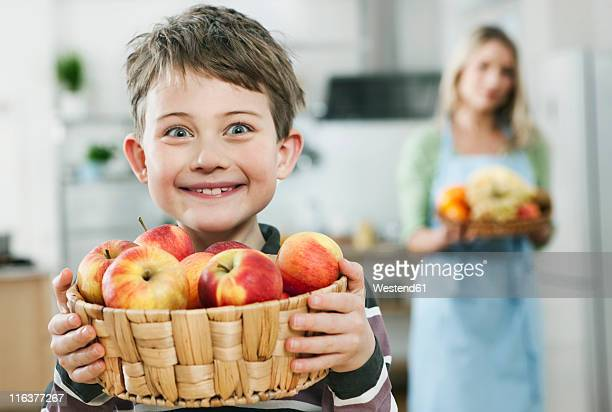 Germany, Cologne, Boy holding apple basket with mother in background