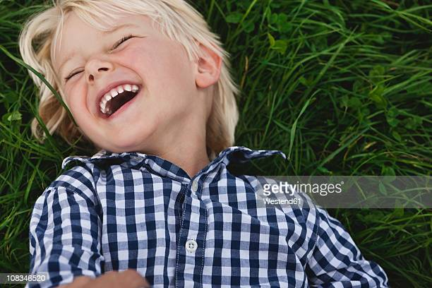 germany, cologne, boy (2-3 years) lying on grass and laughing - 2 3 years stock pictures, royalty-free photos & images