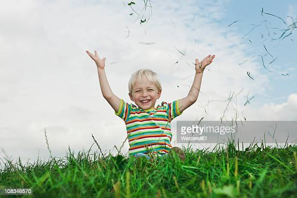 germany, cologne, boy (2-3 years) playing with grass, smiling - werfen stock-fotos und bilder