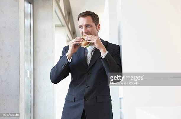 Germany, Cologne, Businessman eating sandwich, portrait