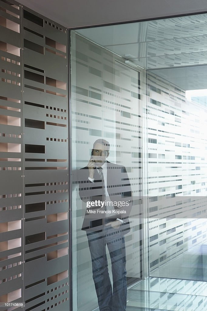 Germany Cologne Businessman Using Mobile Phone Behind Glass Door