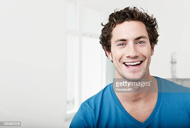 germany, cologne, close up of young man in renovating apartment, smiling, portrait - stralende lach stockfoto's en -beelden