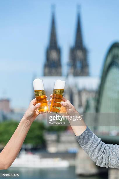 Germany, Cologne, couple toasting with Koelsch glasses
