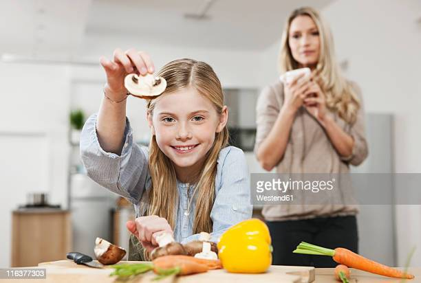 Germany, Cologne, Daughter cutting vegetable with mother in background