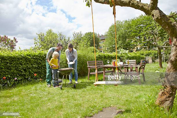 germany, cologne, family having barbecue in garden - gemüsegarten stock-fotos und bilder