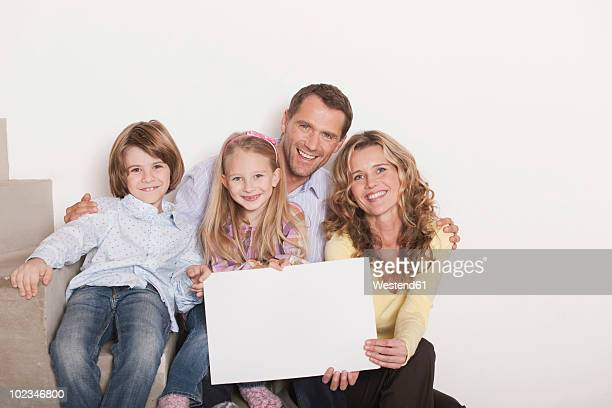Germany, Cologne, Family sitting on steps of staircase using laptop, smiling, portrait