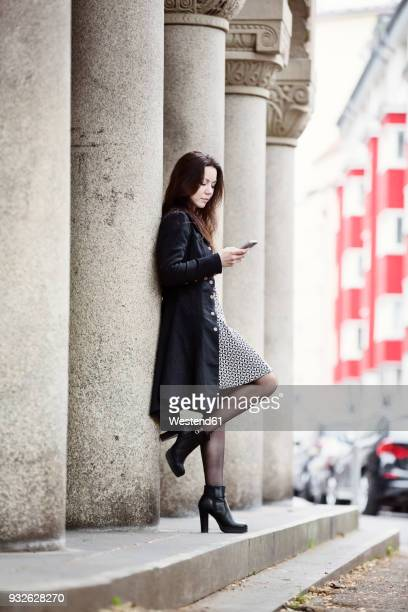 germany, cologne, fashionable young woman leaning against column looking at cell phone - black boot stock pictures, royalty-free photos & images