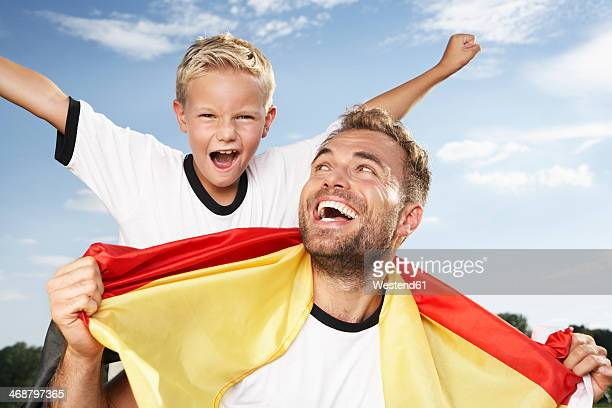 germany, cologne, father and son cheering in football outfit - torcer imagens e fotografias de stock