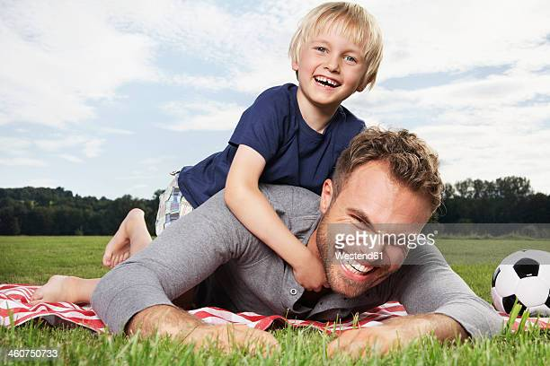 germany, cologne, father and son playing around on picnic blanket - lying on front stock pictures, royalty-free photos & images