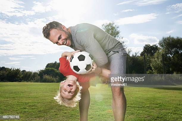Germany, Cologne, Father and son playing soccer