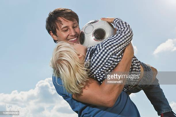 germany, cologne, father and son (2-3 years) playing with ball, smiling - 25 29 years stock pictures, royalty-free photos & images