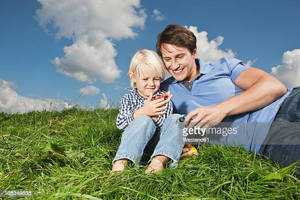 germany, cologne, father and son (2-3 years) playing with toy car, smiling - 25 29 years stock pictures, royalty-free photos & images