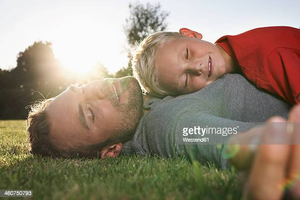 Germany, Cologne, Father and son sleeping in meadow