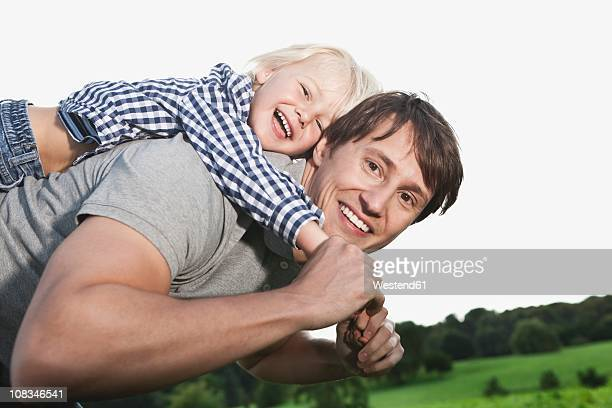 Germany, Cologne, Father carrying piggy back of his son (2-3 Years), smiling, portrait