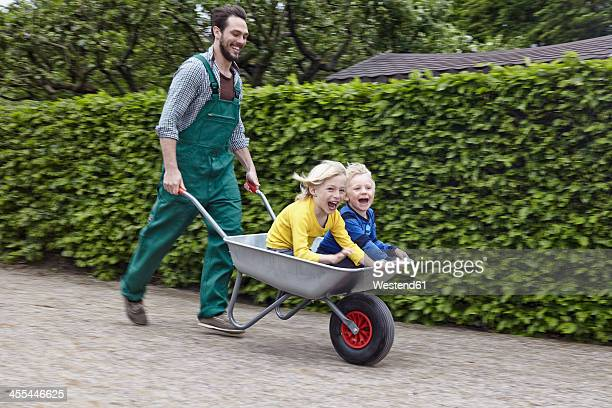 Germany, Cologne, Father carrying son in wheelbarrow, smiling