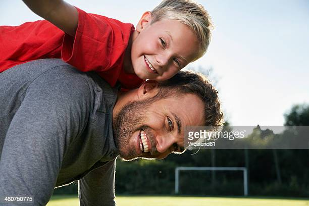 Germany, Cologne, Father carrying son on back, smiling