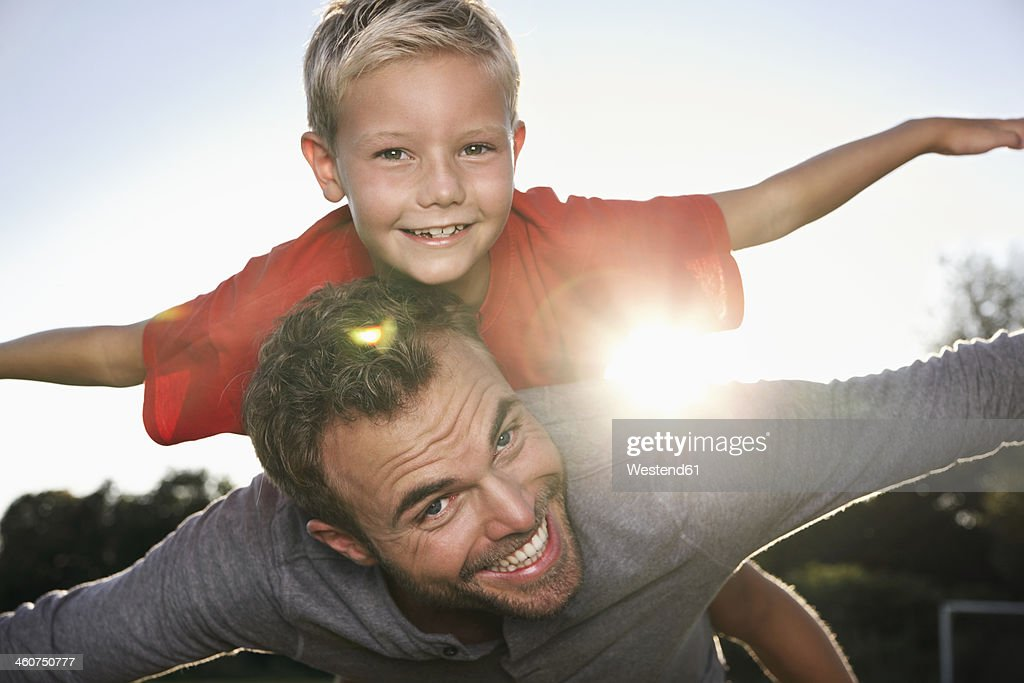 Germany, Cologne, Father carrying son, pretending to fly : Photo