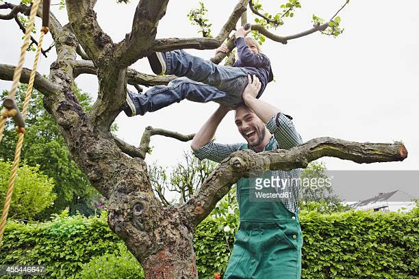 Germany, Cologne, Father helping son to climb tree, smiling