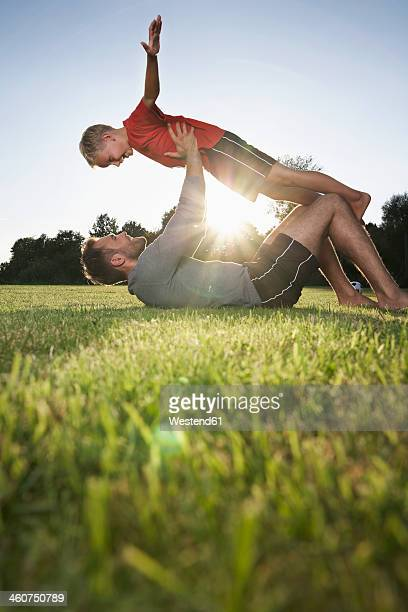 Germany, Cologne, Father holding son aloft on soccer field