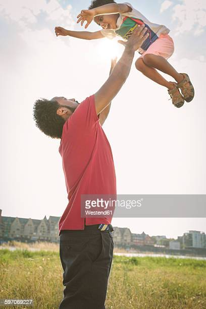 Germany, Cologne, father throwing up his son in a field