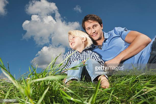 Germany, Cologne, Father with son (2-3 Years) on grass, smiling
