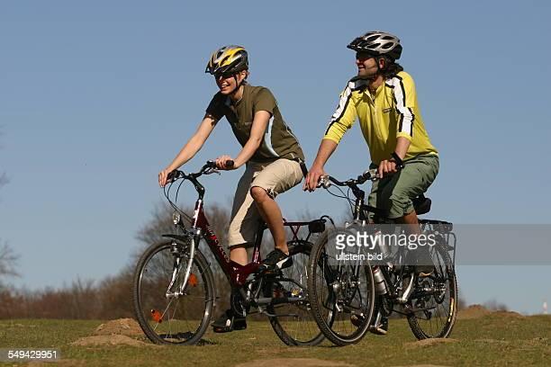 Free time Young couple on their mountainbike tour through the green