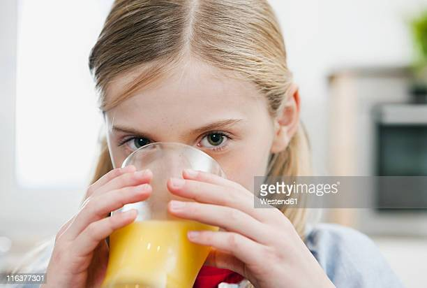 Germany, Cologne, Girl drinking orange juice, portrait