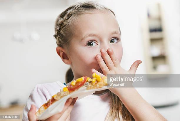 Germany, Cologne, Girl eating a slice of pizza