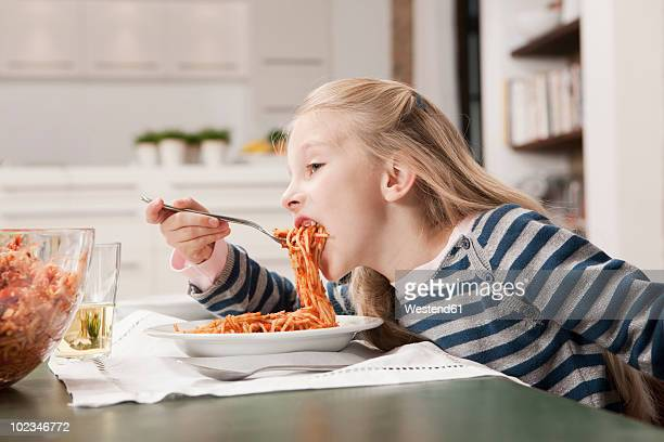germany, cologne, girl (6-7) eating spaghetti, side view, portrait - bolognese sauce stock pictures, royalty-free photos & images